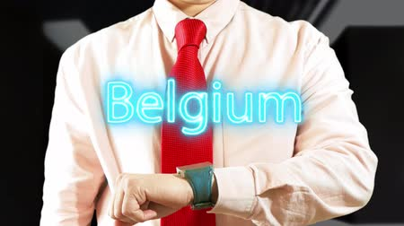 widgets : Belgium. Businessman chooses country on hologram clock on dark background. Visual screen. Futuristic Interface 4K stock footage