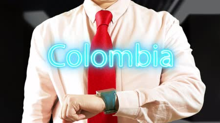 widgets : Colombia.Businessman chooses country on hologram clock on dark background. Visual screen. Futuristic Interface 4k footage clip