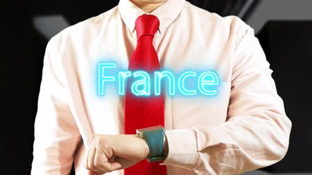 France. Businessman chooses country on hologram clock on dark background. Visual screen. Futuristic Interface 4k footage clip