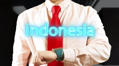 Indonesia. Man working with hologram clock on dark background. Futuristic concept. Augmented reality 4K stock footage Stock Footage