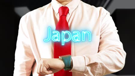 Japan. Businessman operating a smart device on dark background. Concept: business trip,hologram, technology, augmented reality, future, travel 4K stock footage