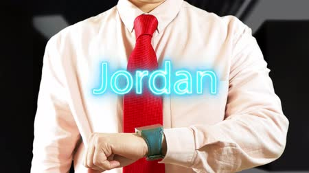 widgets : Jordan. Businessman chooses country on hologram clock on dark background. Concept: business trip,hologram, technology, augmented reality, future, travel 4k footage clip
