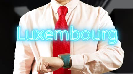 widgets : Luxembourg. Businessman chooses country on hologram clock on dark background. Concept: business trip,hologram, technology, augmented reality, future, travel 4k footage clip Stock Footage
