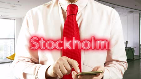 stockholm : Stockholm. Businessman chooses а city on virtual interface in light office. Concept: business trip,hologram, technology, augmented reality, future, travel 4k footage video Stock Footage