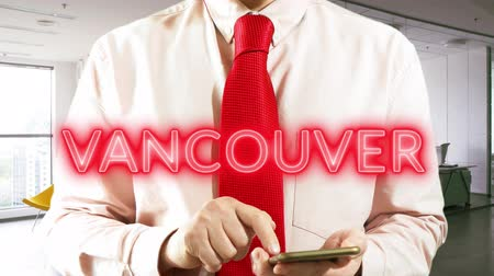 Ванкувер : Vancouver. Businessman chooses а city on virtual interface in light office. Concept: business trip,hologram, technology, augmented reality, future, travel 4k footage video Стоковые видеозаписи