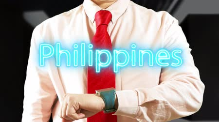 Philippines. Businessman operating a smart device chooses а country. Concept: business trip,hologram, technology, augmented reality, future, travel 4k footage clip