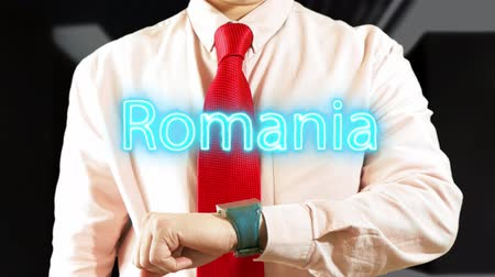 Romania. Businessman chooses country on hologram clock on dark background. Concept: business trip,hologram, technology, augmented reality, future, travel 4K stock footage