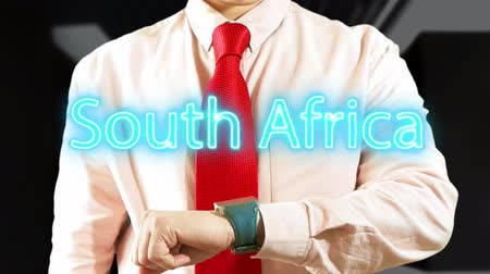 South Africa. Businessman operating a smart device chooses а country. Concept: business trip,hologram, technology, augmented reality, future, travel 4k footage clip Stock Footage