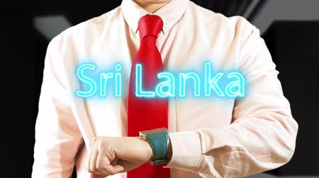 widgets : Sri Lanka. Businessman chooses country on hologram clock on dark background. Concept: business trip,hologram, technology, augmented reality, future, travel 4k footage clip Stock Footage