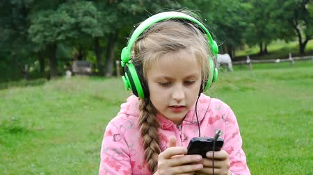 outside : Girl listening to music from a smart phone