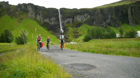 foss : Waterfall at Sidu. Cyclists on the background of a waterfall. Iceland.