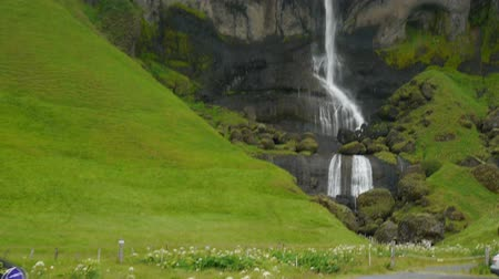 foss : Cyclists ride along the road from the famous waterfall Sidu. Iceland. Stock Footage