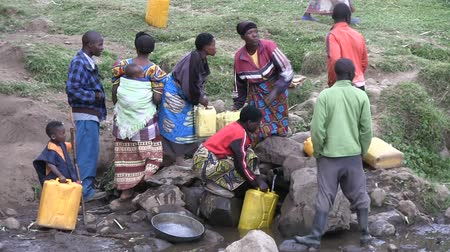 afrika : Local residents collect water in a single source of water near the village