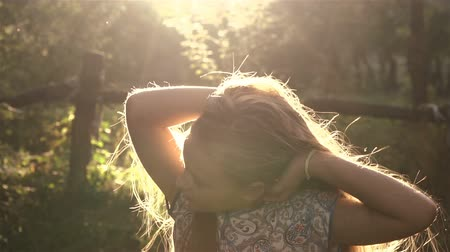 ventoso : Romantic young girl. Girl playing with her hair in the sunlight. Slow Motion 100 FPS.