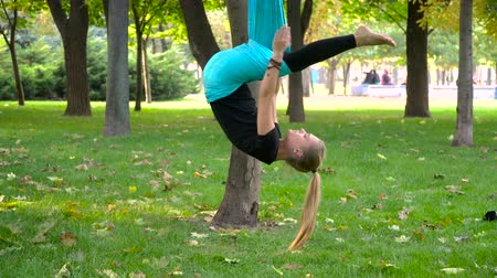 gimnastyka : One type of yoga - aerial yoga. A young girl in a park engaged in aerial yoga. This type of yoga on special fabric canvases