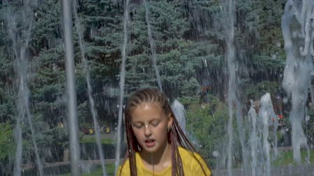roupas : A girl in yellow clothes splashes in a water fountain. The child is playing with water and very happy. Slow motion