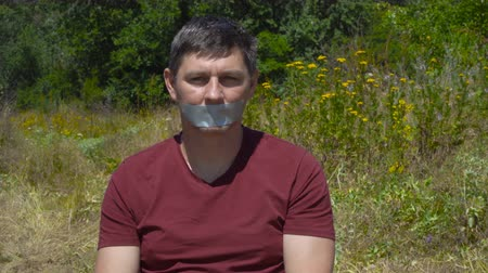 totalitarianism : The mens mouth glued tape.Boy looks at the camera (emotion). This video can be used in films about freedom of speech and democracy Stock Footage