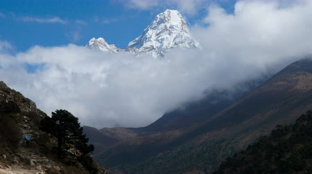 porters : Time lapse. The movement of clouds near the majestic Mount Ama Dablam. Track to the base camp of Everest in the Himalayas. On the trail walk porters and trackers. Sagarmatha National Park, Nepal, 4K Stock Footage