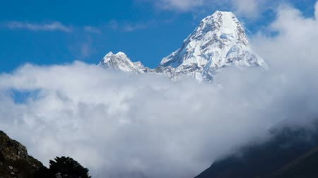 porters : Time lapse. The movement of clouds near the majestic Mount Ama Dablam. Track to the base camp of Everest in the Himalayas. On the trail walk porters and trackers. Sagarmatha National Park, Nepal