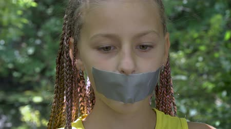 totalitarianism : A girl with a taped mouth. Girl looks at the camera (emotion). This video can be used in films about freedom of speech and democracy