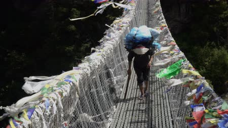 sherpa : Porter with a cargo goes on a suspension bridge. Track to the base camp of Everest in the Himalayas. Sagarmatha National Park, Nepal