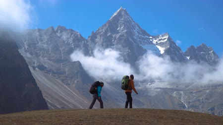 крепление : Backpackers with backpacks travel in the Himalayan mountains. They look at the snowy peaks and are happy with the trip. 4K