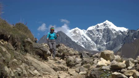 himalaia : Girl tourist walking along the trail in the Himalayan mountains. Beautiful view of the snow-capped mountain peaks