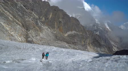 himalája : Two girls climbers go through the glacier in the Himalayas. Difficult climb to the high mountain pass. Nepal. 4K Stock mozgókép