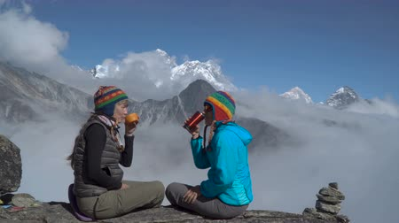 himaláje : The girls sit on a rock and drink tea. They are laughing and happy. Beautiful Himalayan mountains and clouds. 4K
