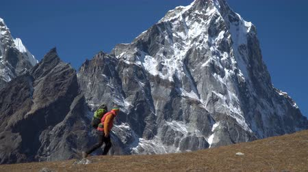 sklon : Man with backpack are walking along the mountain slope in the Himalayas. Enjoys adventure and travel concept. 4K