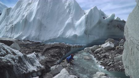 icefall : The Khumbu Glacier descends from Mount Everest. Walking on the glacier is very dangerous. A girl drinks water from a creek. Nepal. Himalayas. 4K