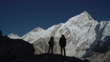wspinaczka : Hikers travel in the Himalayan mountains. They look at the snowy peaks and are happy with the trip. 4K