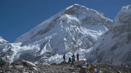 icefall : Tourists stand on the spot where the base camp of Everest is located. The mountain behind them is Mount Everest. The highest mountain in the world. 4K Stock Footage