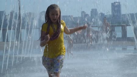 squirting : The girl runs through the fountain. She is happy and laughing. Slow motion