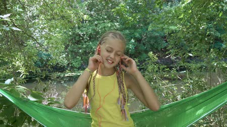 children only : Girl in headphones listening to music. Child is happy and smiling