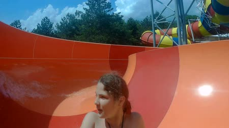 waterslide : ODESSA, UKRAINE - AUGUST 3, 2017: Happy girls going down a waterslide at the water park on August 3, 2017 in Odessa, Ukraine