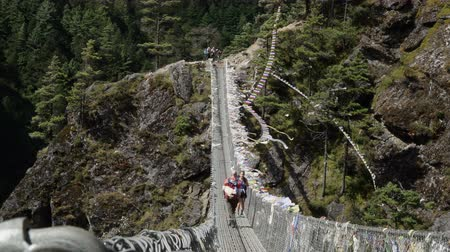 foothills : NAMCHE, NEPAL - OKTOBER 22, 2017: Sherpas and hikers walk a bridge crossing a valley in the foothills of the Himalayas. They travel in mountains and carry big backpacks near Namche village on oktober 22, 2017 in Namche, Nepal