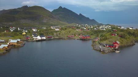İskandinavya : Aerial view of small village in Norway, Sorvagen - fishing village on the lofoten islands, and popular tourist destination with its typical red houses and natural beauty. Aerial 4k Stok Video