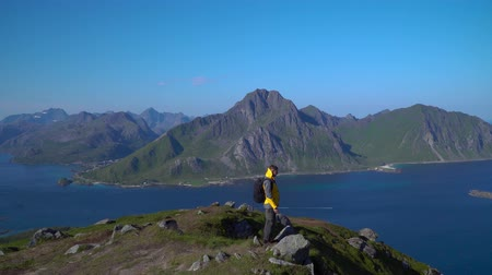 climbed : A man with a backpack climbed to the top of the Lofoten Islands. Adventure and travel concept. Norway. 4k