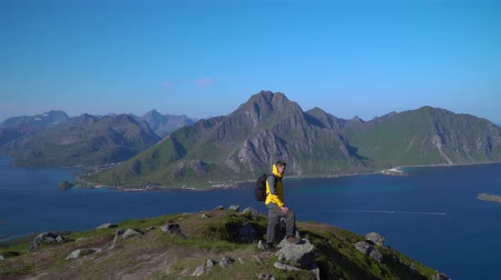 A man with a backpack climbed to the top of the Lofoten Islands. Adventure and travel concept. Norway. 4k