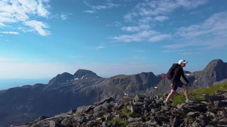 Aerial view of girl with a backpack rises on a mountain ridge. Beautiful view of the peaked tops of the Lofoten Islands. Norway 4k Stok Video
