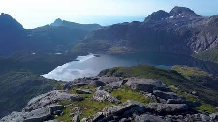 Aerial view of girl with a backpack rises on a mountain ridge. Beautiful mountains of the Lofoten Islands. Norway 4k 무비클립
