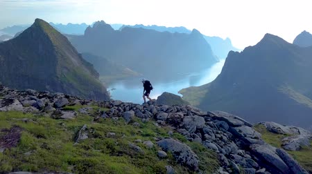 Aerial view of girl with a backpack rises on a mountain ridge. Beautiful view of the peaked tops of the Lofoten Islands. Norway 4k Stock Footage