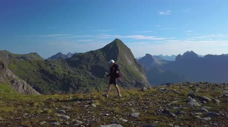 caminhadas : A girl with a backpack travels in the mountains. Beautiful view of the peaked tops of the Lofoten Islands. Norway 4k