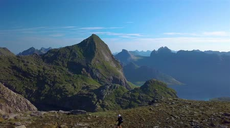 Aerial view of girl with a backpack travels in the mountains. Beautiful view of the peaked tops of the Lofoten Islands. Norway 4k