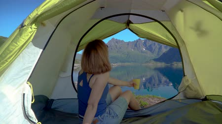 Happy woman sitting in a tent. Beautiful views of the mountain peaks and the sea bay. Lofoten. Norway. 4K Wideo