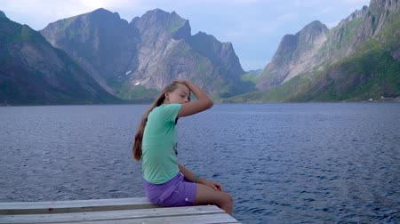 Beautiful happy girl sits on the dock and looks at the mountains and the sea. Norway. Lofoten Islands.