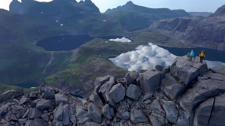 alpinism : Aerial - Flying around tourists on peak of a high mountain. Lafoten islands. Norway 4k Stock Footage