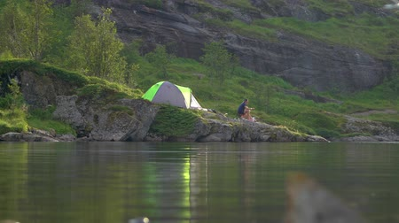 İskandinavya : Tourists are resting near the tent. The tent is located on the shore of a beautiful mountain lake. Seagulls fly over the water. The beautiful nature of Norway. Lofoten Islands.