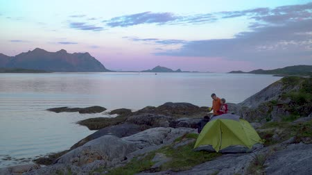 İskandinavya : Father and daughter near a tent on the shore of the Norwegian fjord. Beautiful view of the mountains and the sea bay. Lofoten. Norway. 4K